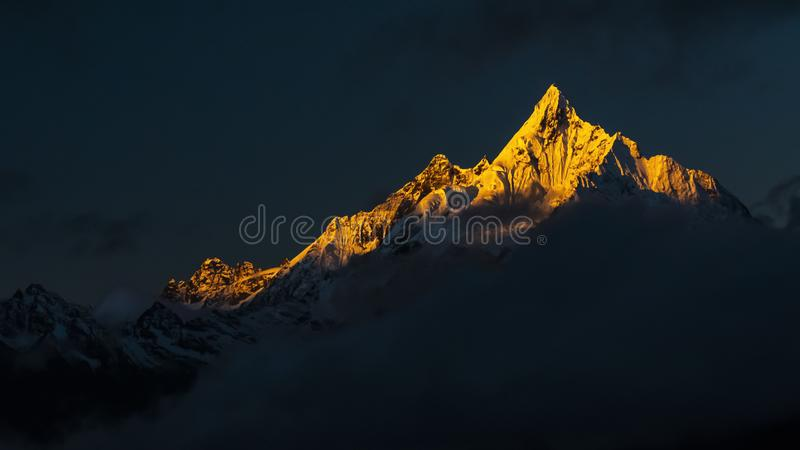 The first sun shines on the snow peak. Meili Snow Mountain is located in the northwestern part of Yunnan Province, China. The main peak Kawagbo is 6,740 meters royalty free stock image