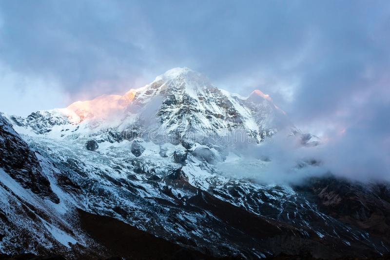 First sunbeams lighting the peak of Mount Annapurna South 7219 m on sunrise, Annapurna Base Camp , Annapurna Conservation Area stock photo
