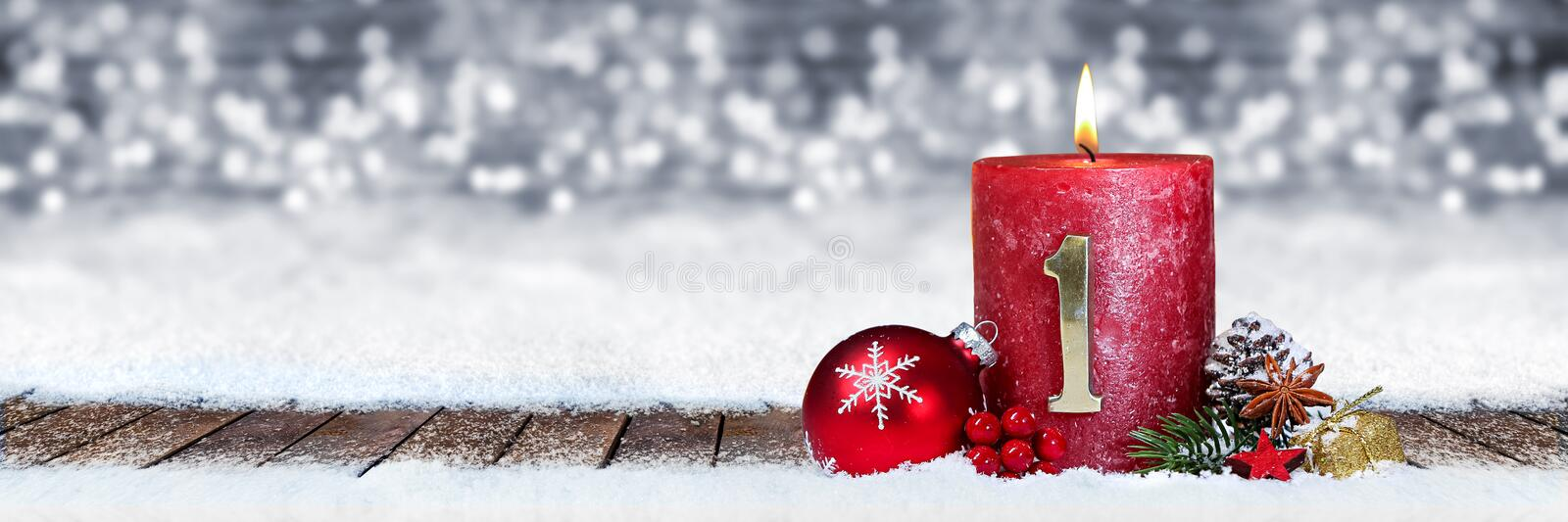 First sunday of advent red candle with golden metal number one on wooden planks in snow front of panorama bokeh background. First sunday of advent red candle stock photos