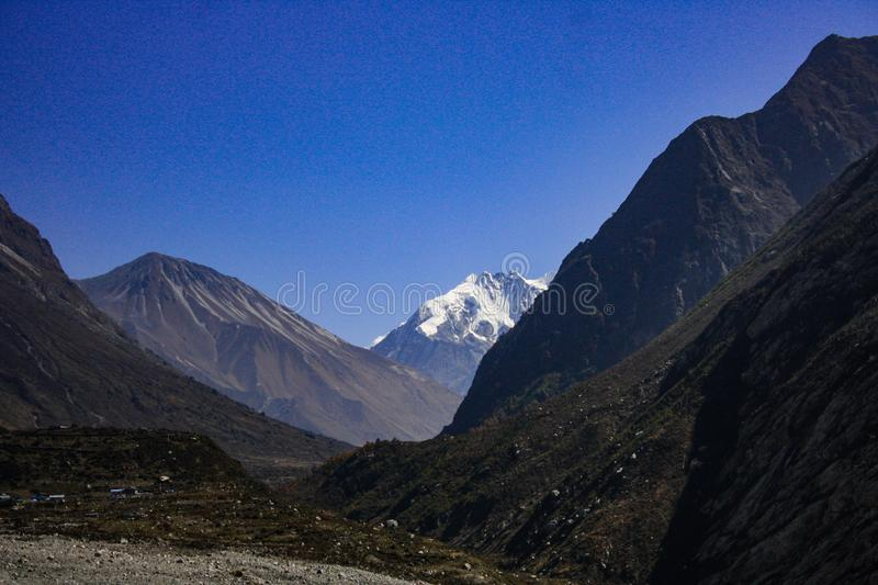 Tsergo-Ri first view from Langtang Valley. The first view of Tsergo Ri from Langtang Valley with snowcapped mountains in the distant horizon and black stone stock photo
