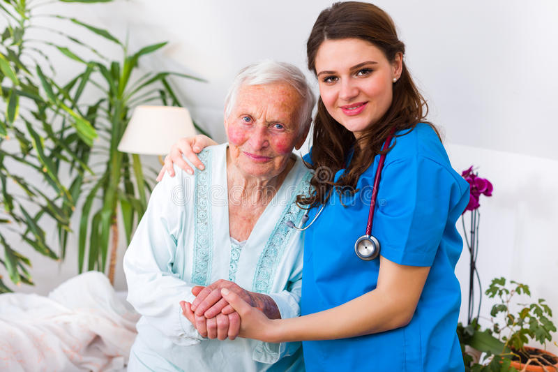 The first walk after long time with doctor. Caring nurse supporting her patient when she is getting up from bed after long time of illness stock photos