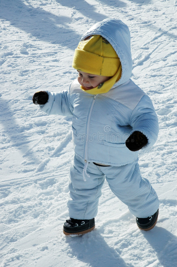 Firt steps in the snow. A little and smiling baby takes his first steps in the snow stock image