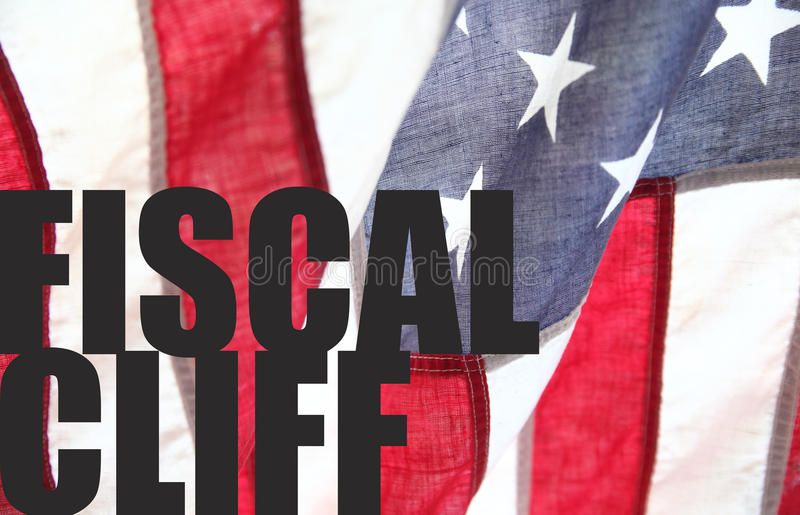 Fiscal cliff words on USA flag. The words 'fiscal cliff' on an old American flag stock image