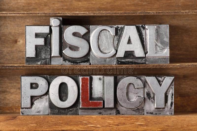 Fiscal policy tray. Fiscal policy phrase made from metallic letterpress type on wooden tray royalty free stock images