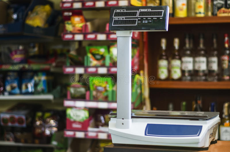 Fiscal weight. Fiscal weight, high arm, electronic display. The balance stands on the counter, in the background store shelves, a lot of goods royalty free stock photos