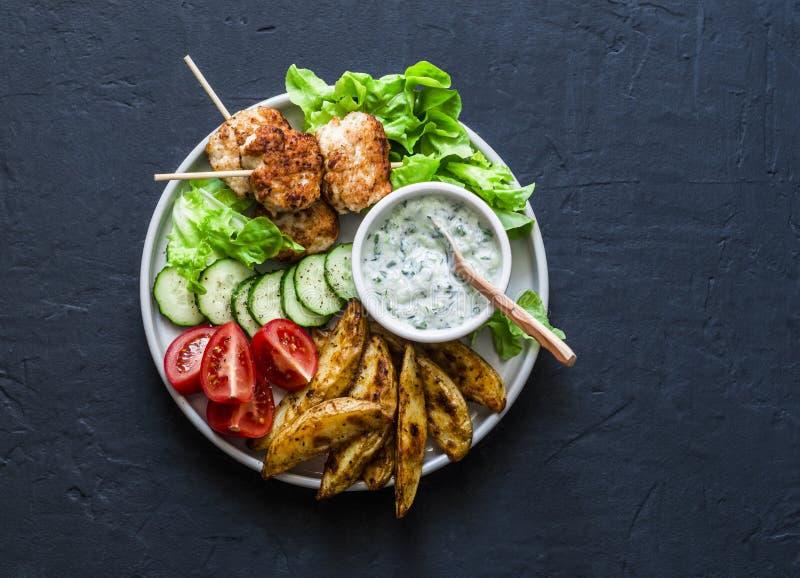 Fischaufsteckspindeln, Ofenkartoffeln, Gemüse und Jogurtgrünsoße auf dunklem Hintergrund, Draufsicht stockbilder