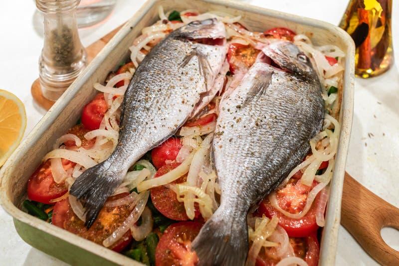 Fische, vorbereitet für das Backen auf Gemüsekissen im Metallbackblech auf weißer Tabelle lizenzfreie stockfotografie