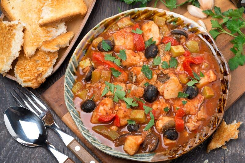 Fischeintopfgericht in der Tomatensauce auf einer Platte, Draufsicht lizenzfreie stockfotos