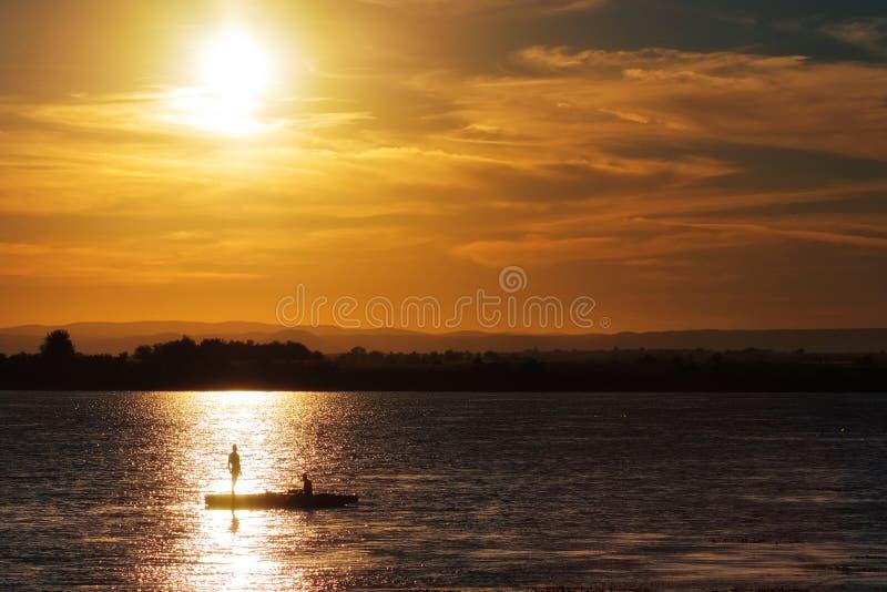 Fischen mit zwei Fischern auf dem See am Sonnenuntergang stockfotos