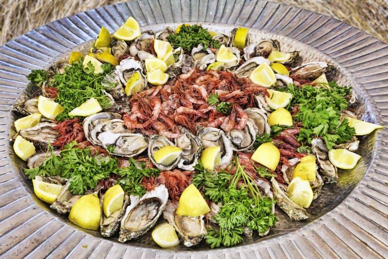 Fischen Sie crudités auf Servierteller mit der Garnele und Austern, die mit Petersilie und frischer Zitrone geschmückt werden stockfotografie
