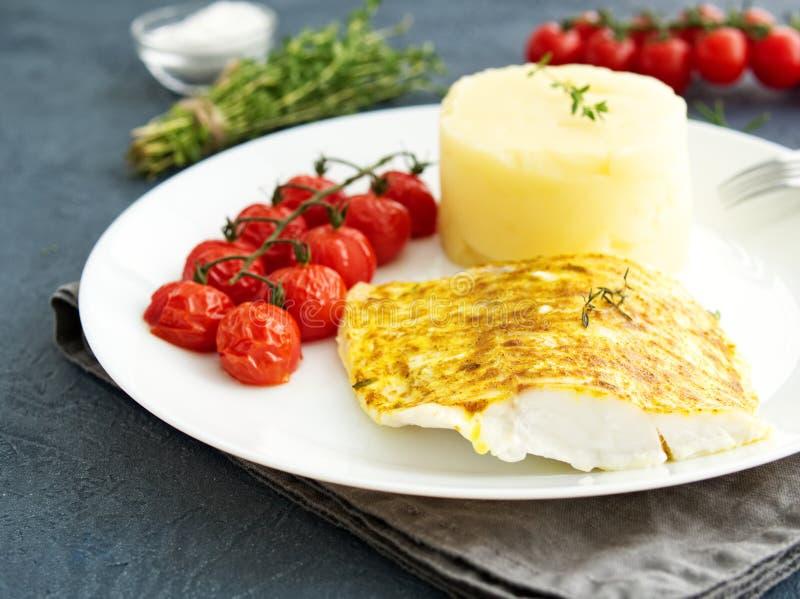 Fischen Sie den Kabeljau, der im Ofen mit Kartoffelpürees, Tomaten gebacken wird, nähren Sie gesundes Lebensmittel Dunkelgrauer H lizenzfreies stockfoto