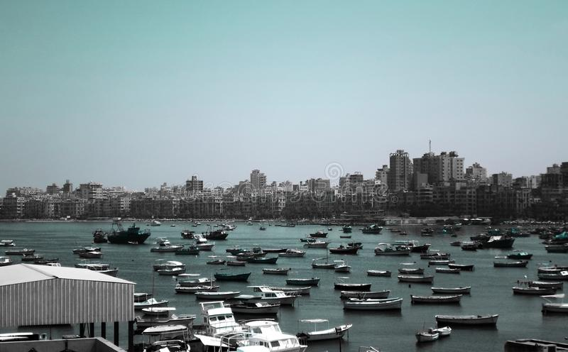 Fischen Sie die Boote, die nahe der Zitadelle von Qaitbay auf der Küste von Alexanderia parken lizenzfreie stockbilder