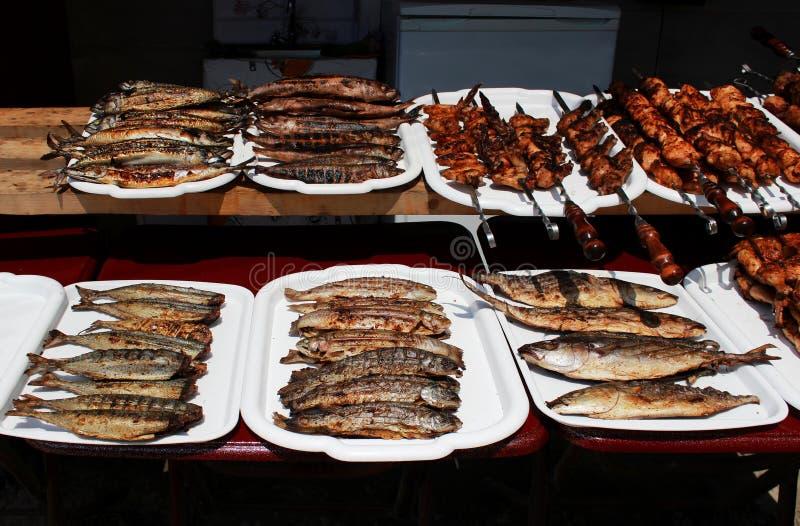fischen Sie ganzes gegrillt auf einem Grill und einem Fleisch auf den Aufsteckspindeln, die völlig auf einer offenen Feuerlüge au lizenzfreie stockbilder