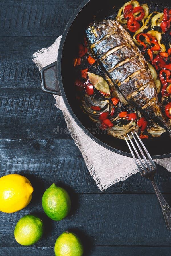 Fischen Sie mit Rosmarin, Zitrone, Tomate auf Pergamentpapier auf einem schwarzen hölzernen Hintergrund, gesundes Lebensmittel au stockfotos