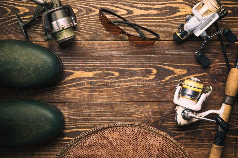 Fischenkonzept Angelrute und Spulen mit den Gummistiefeln, polarisiert, Gläser und Käfig auf hölzernem Hintergrund mit freiem Rau lizenzfreie stockfotografie