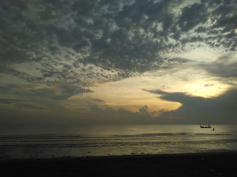 Fischenzeit? Angler im See, nahe zu Sonnenuntergang lizenzfreies stockfoto