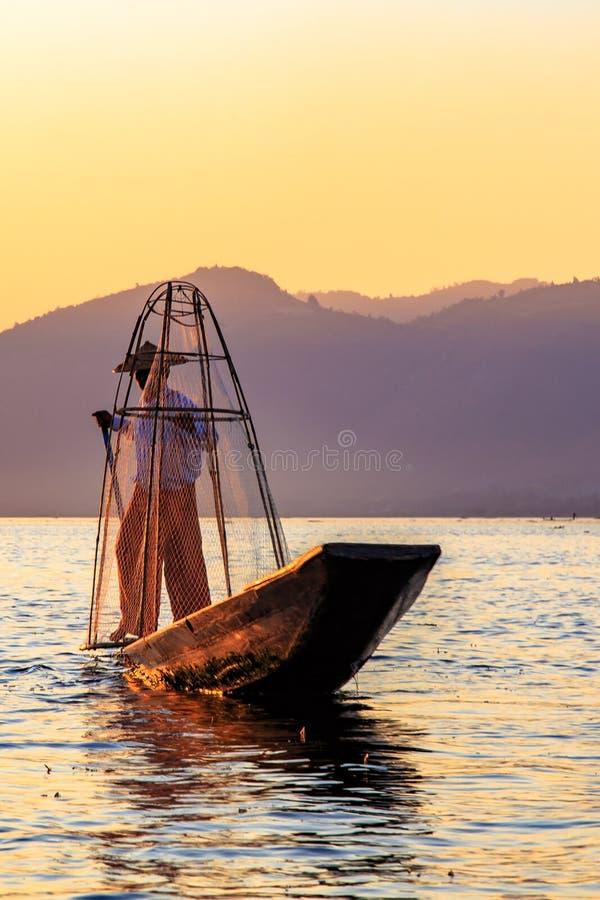 Fischer auf Bambusboot f?ngt Fische durch traditionelles handgemachtes Netz Foto gemacht auf Inle See, Myanmar Birma lizenzfreies stockfoto