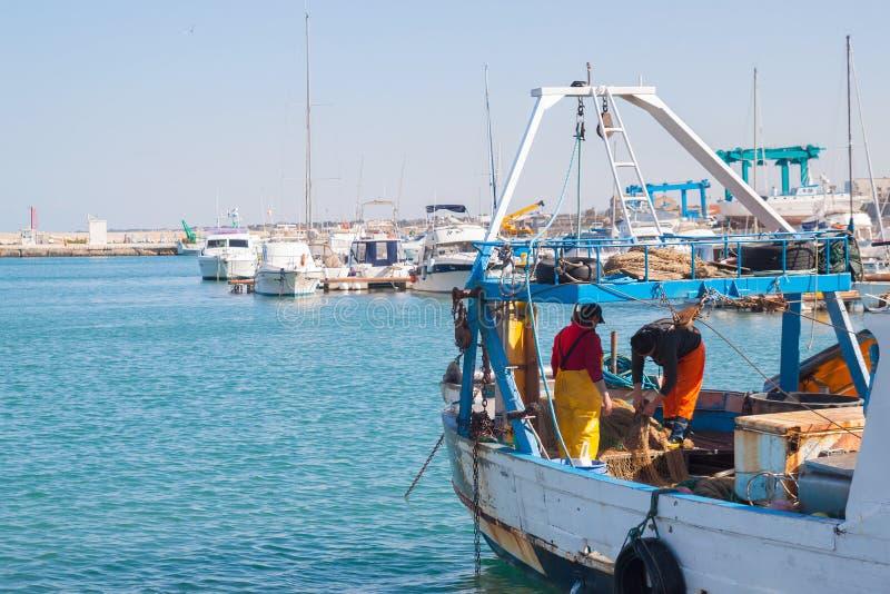 Fischer auf Boot mit Fischernetzen lizenzfreie stockfotos