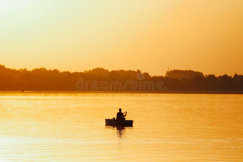 Fischer auf Bootsfischen während des Sonnenuntergangs stockbild