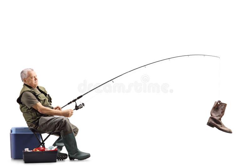 Fischer auf einem Stuhl mit einem alten Stiefel auf der Angelrute stockbilder