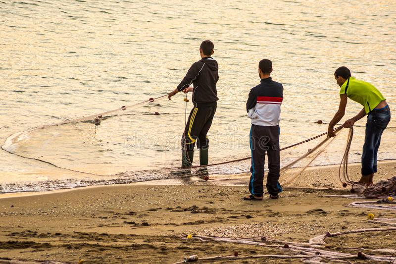 Fischer auf fangenden Fischen der Küste in den Netzen im Sonnenaufgang, MDiq, Marokko stockbild