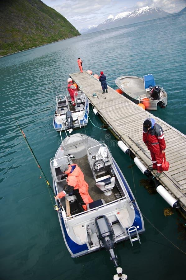 Fischer auf Pier mit Booten lizenzfreie stockbilder