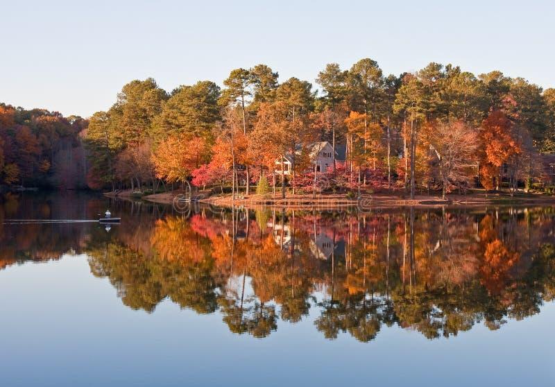 Fischer auf ruhigem See durch Home im Herbst stockbilder