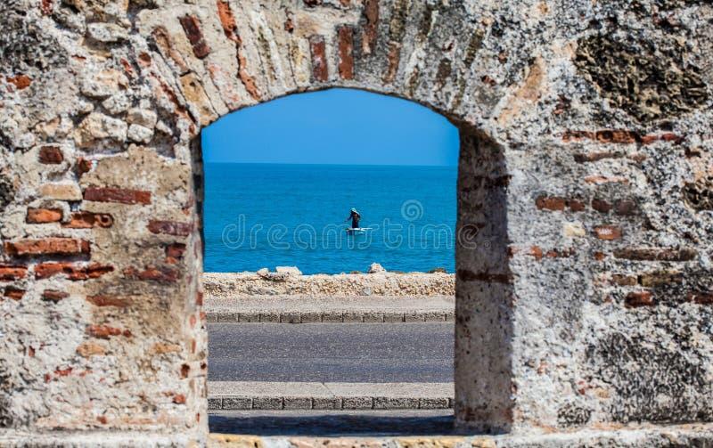 Fischer auf seinem Boot durch gesehen dem Embrasure der Stadtmauern im Cartagena stockfoto