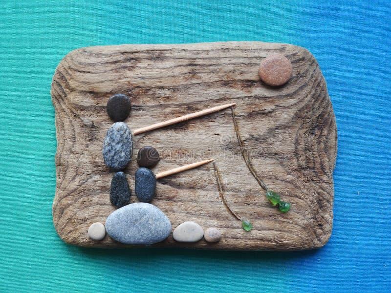 Fischer bemannt Bild unter Verwendung des Seeholzes, der Steine und des Glases, Litauen lizenzfreie stockbilder