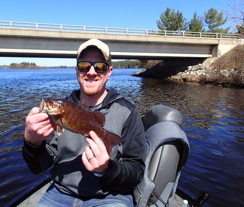 Fischer, der einen kleinen Mund-Baß hält stockfoto