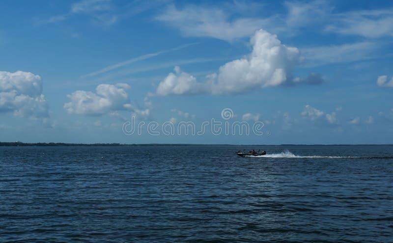 Fischer, der entlang auf einen See beschleunigt stockbilder