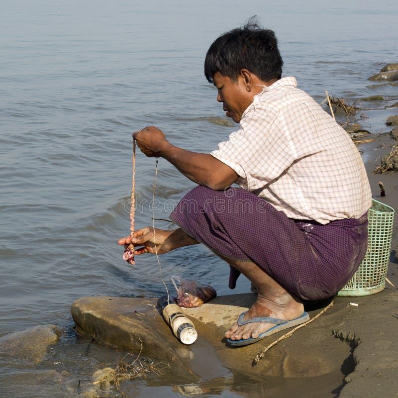 Fischer, der Köder für Fische hakt lizenzfreie stockfotos