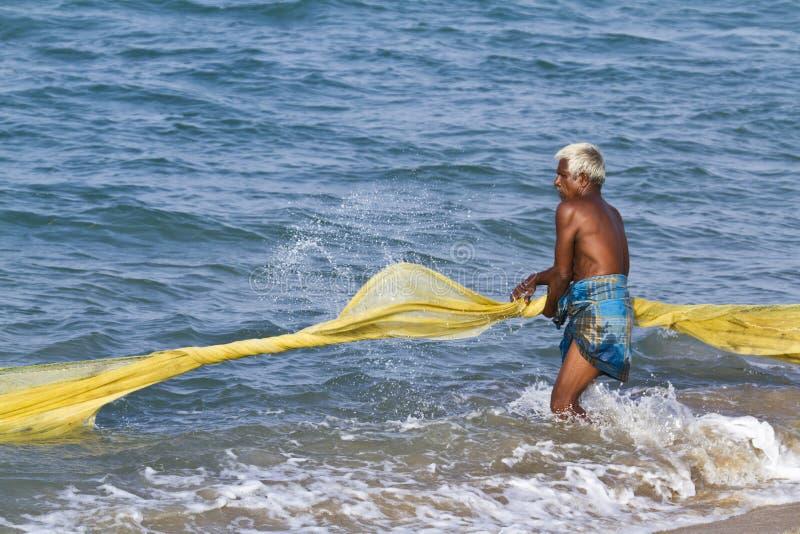 Fischer, der Netz vom Strand in Sri Lanka zieht stockfoto