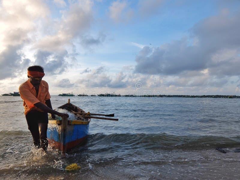 Fischer, der sein Boot auf den Strand nach der Fischerei zieht stockfoto