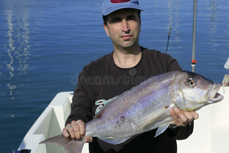 Fischer, der stolze FangSalzwasserfische zeigt lizenzfreies stockbild