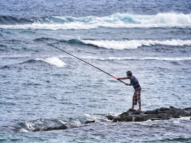 Fischer, die auf Felsen stehen und den Wellen mit Angelruten trotzen lizenzfreies stockfoto