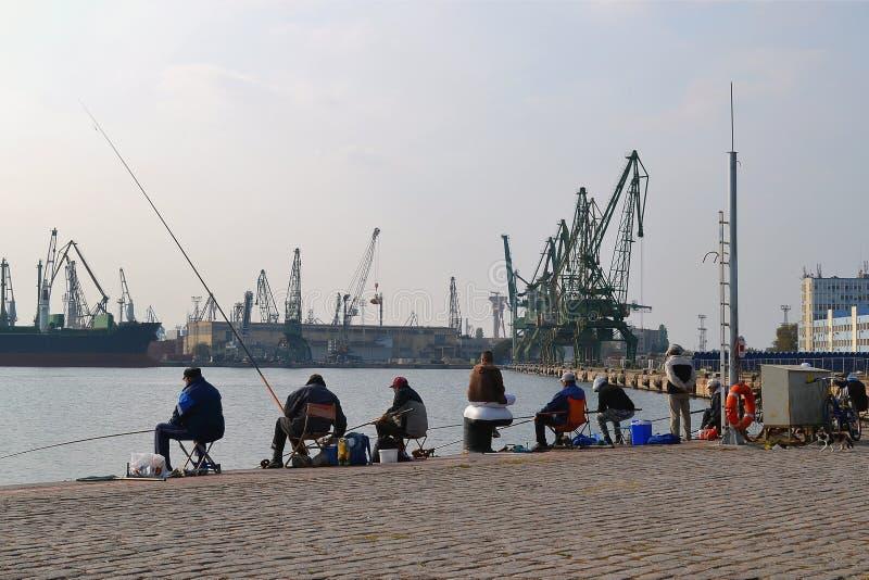 Fischer, die mit einer Stange am Pier im Seehafen an einem warmen windstillen Herbsttag fischen stockfoto