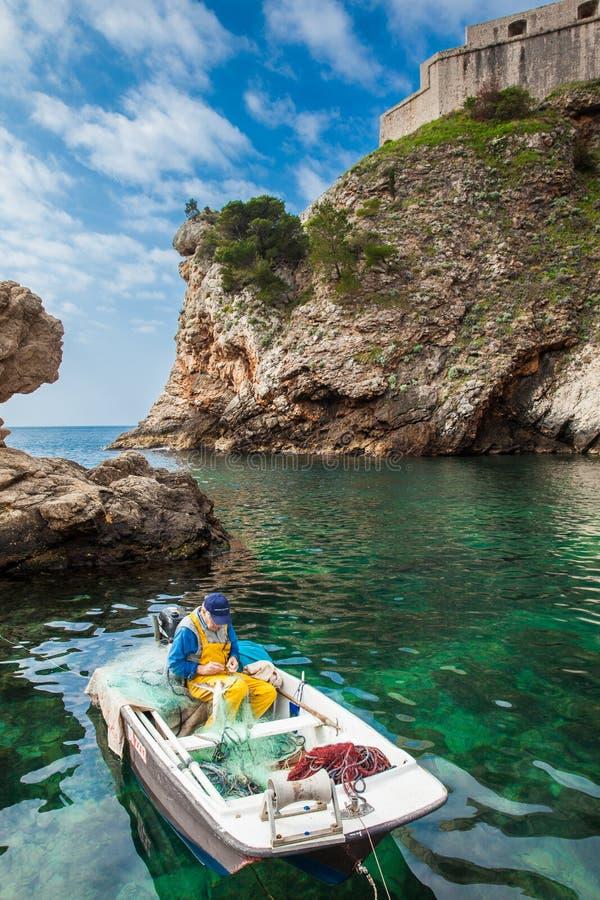 Fischer an Dubrovnik-Westpier und das mittelalterliche Fort Lovrijenac gelegen auf der Westwand der Stadt lizenzfreies stockbild