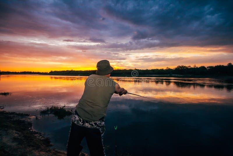 Fischer durch den Fluss auf einem Sonnenunterganghintergrund lizenzfreie stockbilder