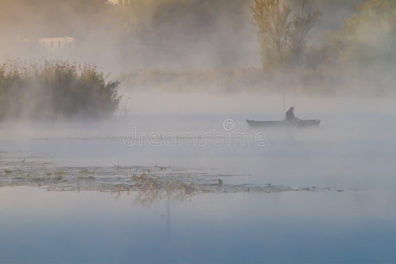 Fischer in einem Bootschiff mit Stangen, dicken Nebelbedeckungen, die noch auf einem Fluss liegen, Bulrush, Rohre und Weiden wach stockfoto