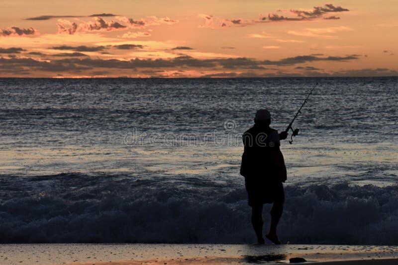 Fischer im Schattenbild bei Sonnenuntergang stockfotos