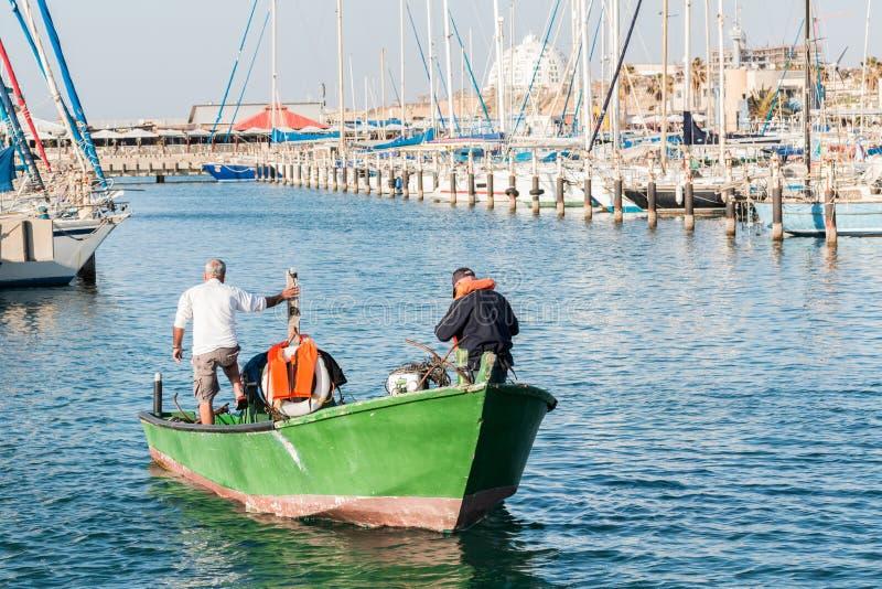 Fischer, mit einem grünen Boot, am Strand in Ashkelon, Israel stockbild