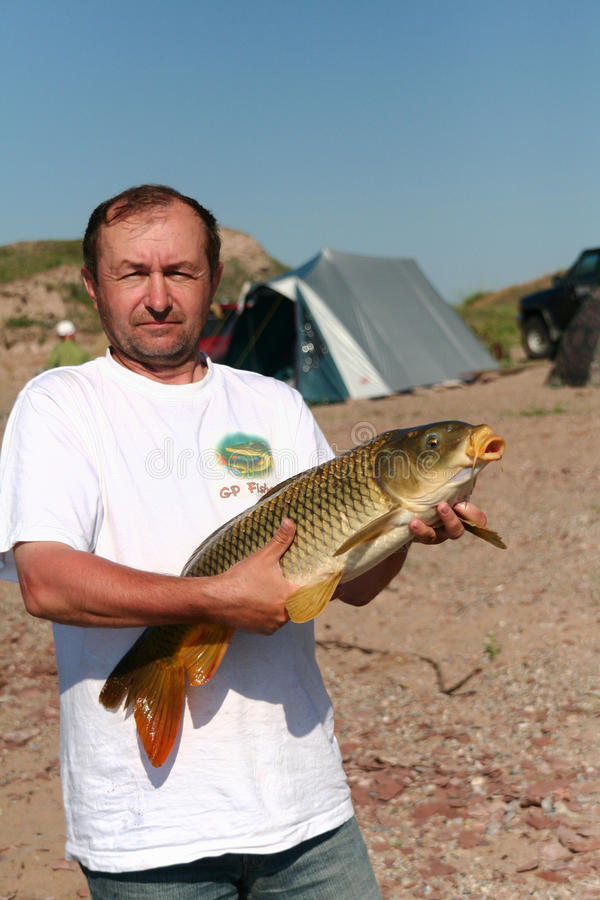 Fischer mit einem großen Karpfen stockfotografie