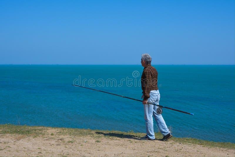 Fischer mit einer Stange auf dem Meer stockbild