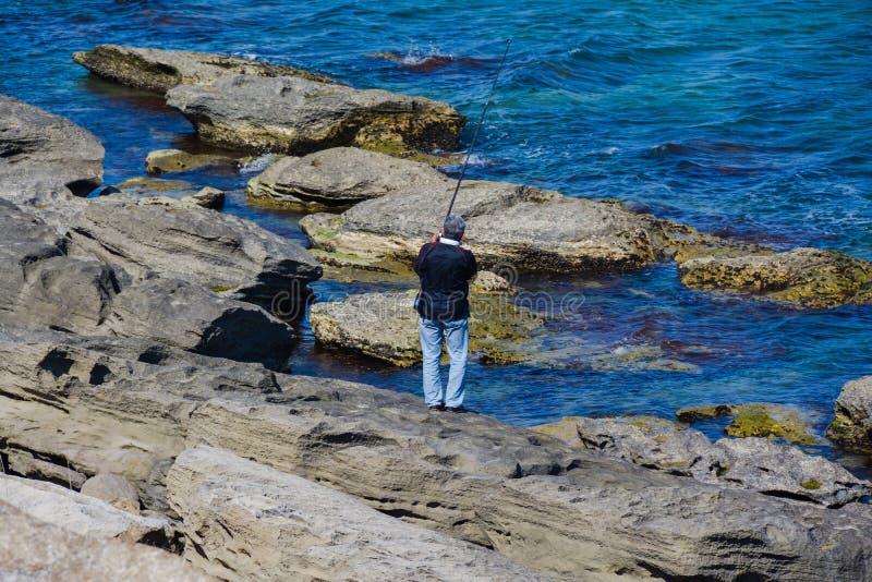 Fischer mit einer Stange auf Felsen im Meer lizenzfreie stockbilder