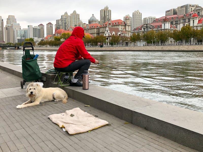Fischer mit seinem Hund auf dem Damm des Flusses Haihe in Tianjin-Stadtzentrum, China lizenzfreies stockbild