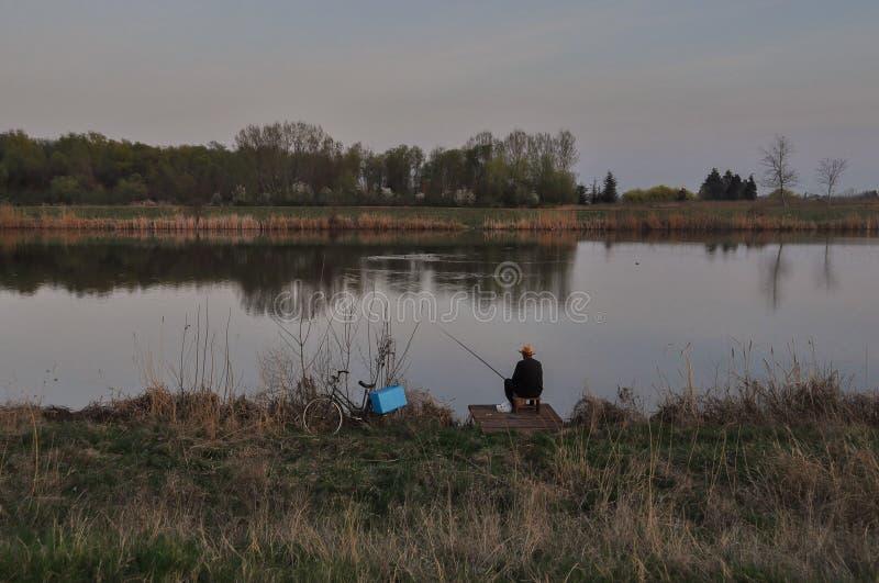 Fischer am ruhigen Abend auf dem Fluss Tisa lizenzfreie stockfotografie