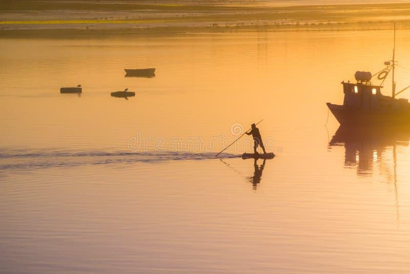 Fischer Silhouette Sonnenaufgang im Hafen von Quellon in Chilo lizenzfreies stockbild