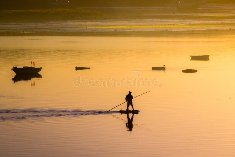 Fischer Silhouette Sonnenaufgang im Hafen von Quellon in Chilo lizenzfreie stockbilder