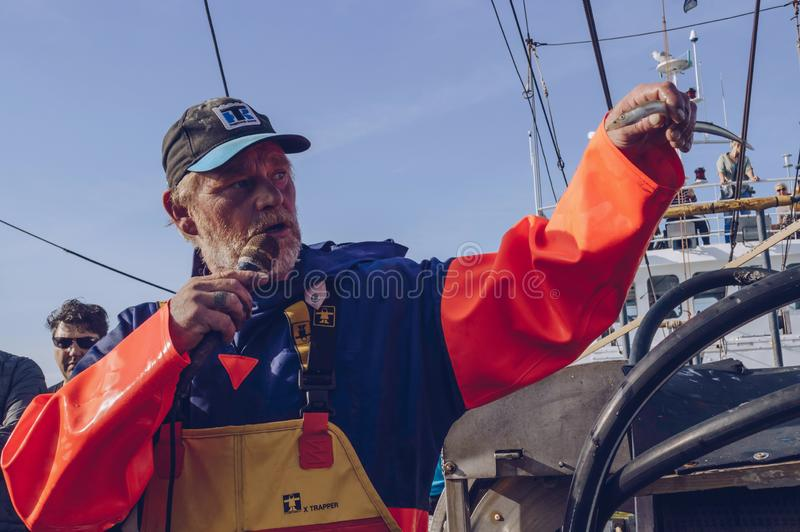Fischer spricht über bestimmte Fischspezies, der im Meer nahe Texe gefangen wird lizenzfreie stockfotografie
